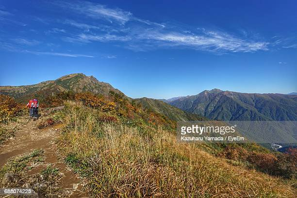 rear view of hikers walking on mountain against sky - maebashi city stock photos and pictures