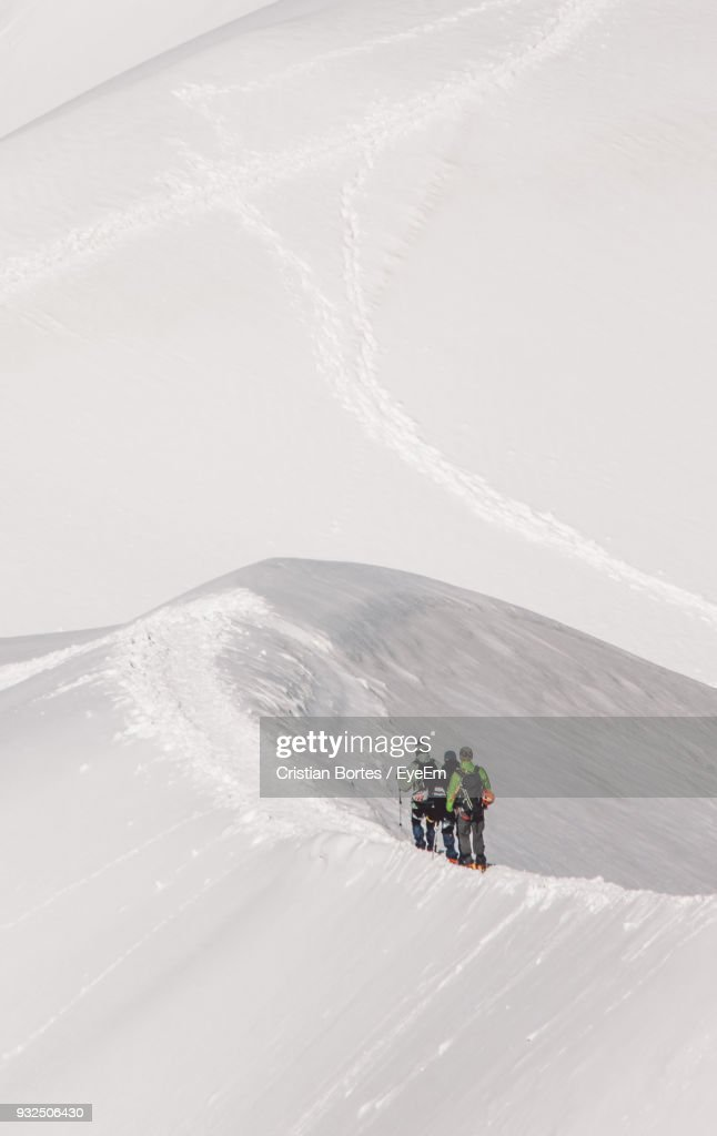 Rear View Of Hikers Walking On Snowcapped Mountain : Foto de stock