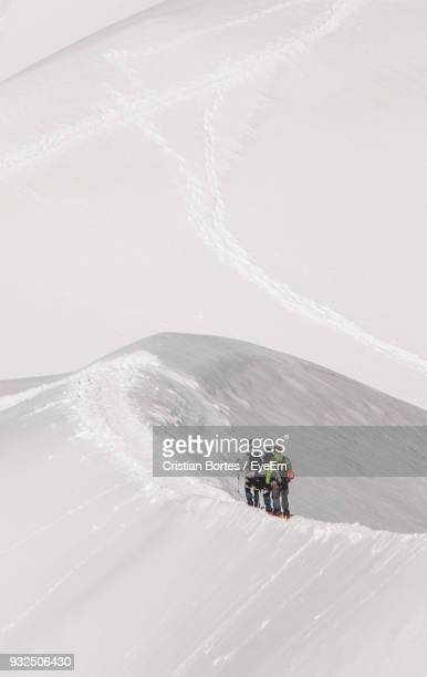 rear view of hikers walking on snowcapped mountain - haute savoie fotografías e imágenes de stock