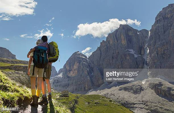 Rear view of hiking couple looking over valley, Brentei Hut, Brenta Dolomite, Italy