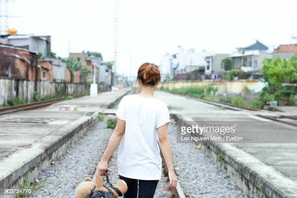 rear view of holding teddy bear while walking on railroad track - bear tracks stock photos and pictures