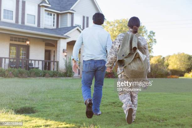 rear view of husband leading military wife back home - military spouse stock pictures, royalty-free photos & images