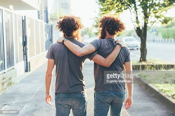 rear view of identical male adult twins strolling on sidewalk - arm around stock pictures, royalty-free photos & images