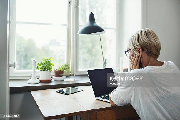 Rear view of industrial designer using laptop at home office