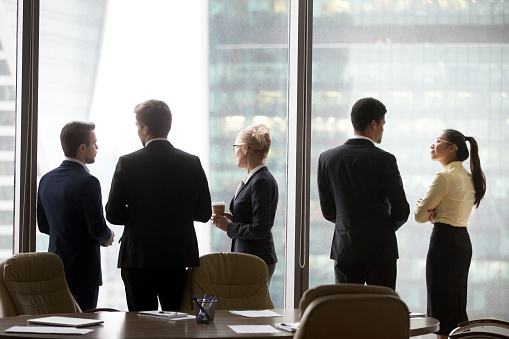 Rear view of international executives team talking near office window 1129629316