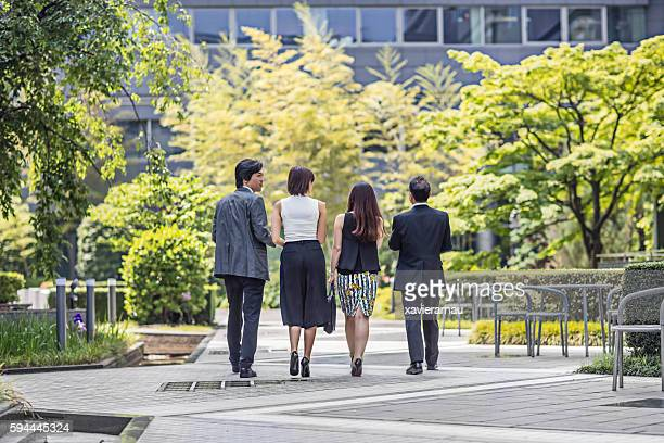 rear view of japanese business people walking to the office - endast vuxna bildbanksfoton och bilder