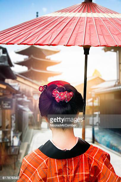 Rear view of Japanese lady walking under umbrella in Kyoto
