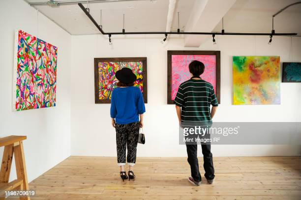 rear view of japanese man and woman looking at abstract painting in an art gallery. - ええじゃないか 発祥の地 ストックフォトと画像