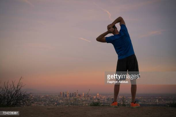 rear view of jogger stretching at dusk, runyon canyon, los angeles, california, usa - precalentamiento fotografías e imágenes de stock