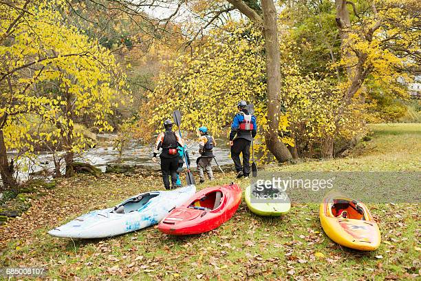Rear view of kayakers walking down river bank, River Dee, Llangollen, North Wales