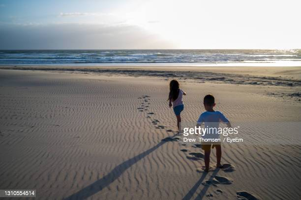 rear view of kids on beach walking towards sunrise - footprint stock pictures, royalty-free photos & images