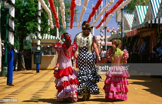 rear view of lady and girls wearing colourful flamenco dresses at feria de abril (april fair). - seville stock pictures, royalty-free photos & images