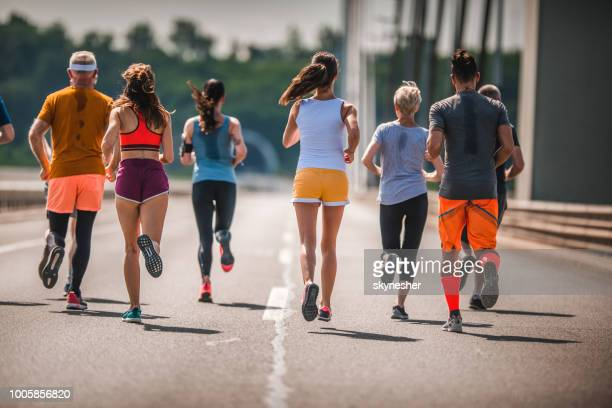 rear view of large group of athletes running a marathon on the road. - half_marathon stock pictures, royalty-free photos & images