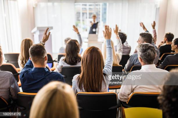 rear view of large group of business people raising arms on a seminar. - q&a stock pictures, royalty-free photos & images