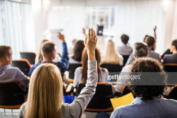 rear view of large group of business people raising hands on a seminar. - asking stock pictures, royalty-free photos & images
