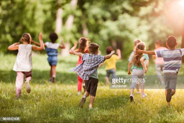 Rear view of large group of children running in springtime.