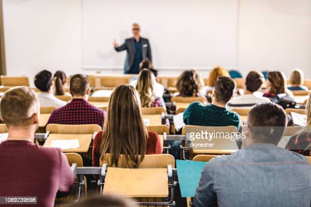 rear view of large group of students on a class at lecture hall. - attending stock pictures, royalty-free photos & images