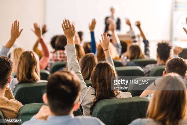 rear view of large group of students raising arms during a class at amphitheater. - q&a stock pictures, royalty-free photos & images