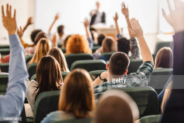 rear view of large group of students raising arms during a class at amphitheater. - college student stock pictures, royalty-free photos & images
