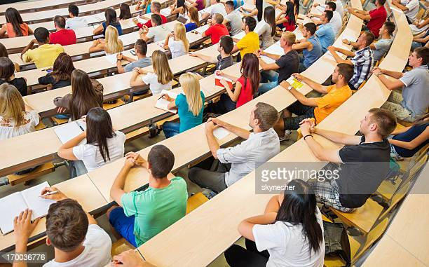 rear view of large group  students at university amphitheatre. - classroom stock pictures, royalty-free photos & images