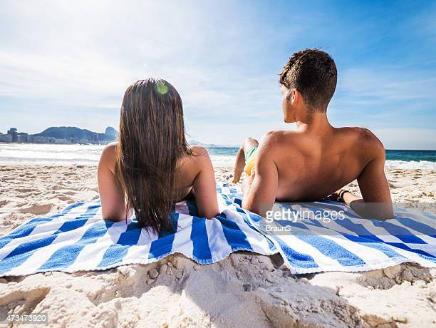 Rear view of Latin American couple relaxing on the beach.