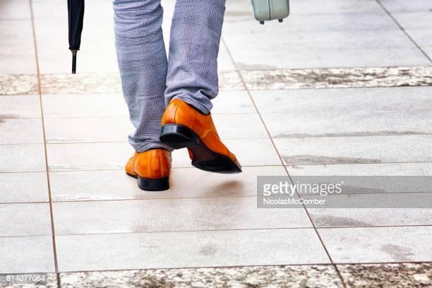 革の靴鞄と傘と濡れた歩道の上を歩いての背面図 - レザー・シューズ ストックフォトと画像