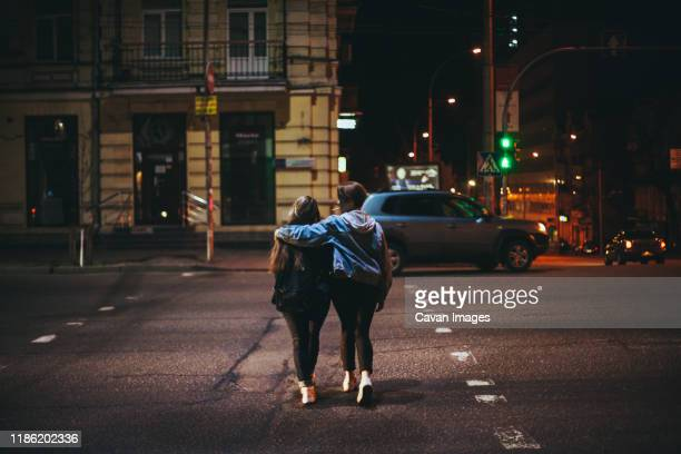 rear view of lesbian couple crossing road in city at night - lesbian dating stock pictures, royalty-free photos & images