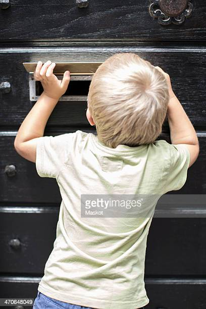 Rear view of little boy looking through mail slot of door