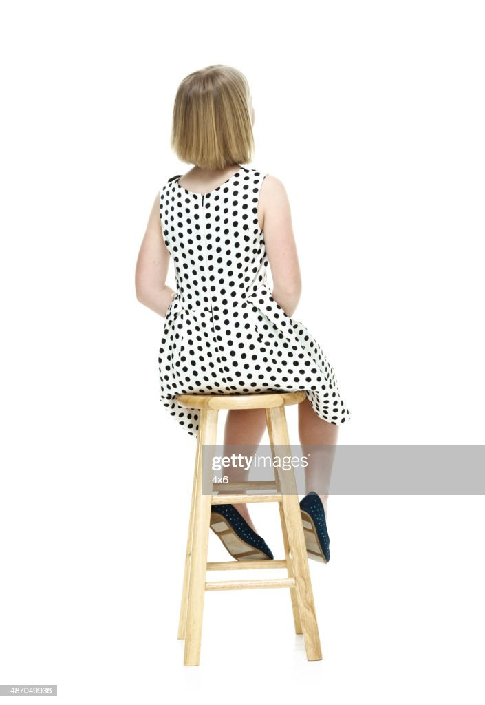 Rear View Of Little Girl Sitting On Stool Stock Photo