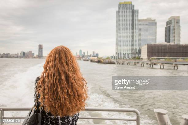 rear view of long red haired businesswoman on ferry deck looking out at skyline, new york, usa - ponte di una nave foto e immagini stock