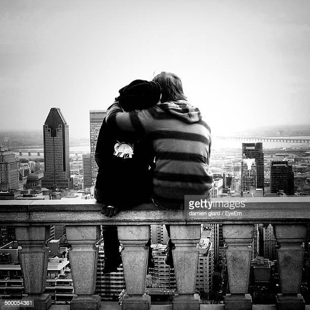 Rear view of loving couple overlooking cityscape