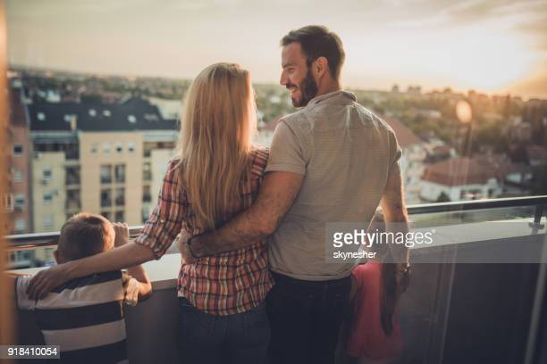 rear view of loving family enjoying a day on a terrace. - penthouse girls stock pictures, royalty-free photos & images