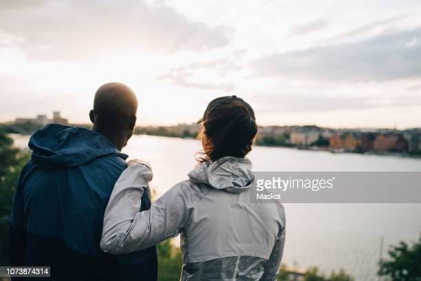 rear view of male and female athletes looking at sea while standing on hill - hand on shoulder stock pictures, royalty-free photos & images