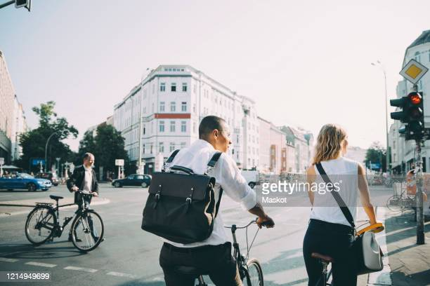 rear view of male and female colleagues standing with bicycle on road in city - berlin stock pictures, royalty-free photos & images