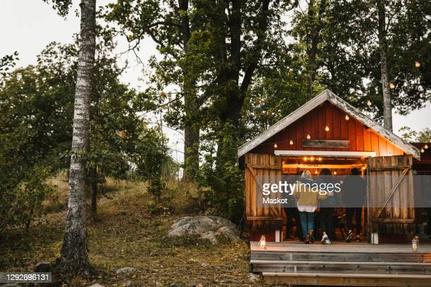 rear view of male and female friends entering cottage during social gathering - sweden stock pictures, royalty-free photos & images