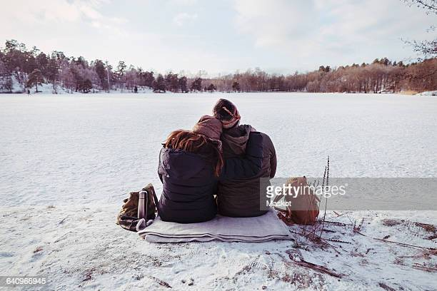 Rear view of male and female hiker sitting on snow covered field