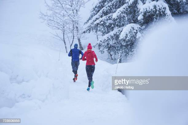 rear view of male and female runners running on track in deep snow, gstaad, switzerland - gstaad stock pictures, royalty-free photos & images