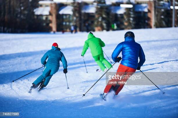 Rear view of male and female skiers skiing down snow covered ski slope, Aspen, Colorado, USA