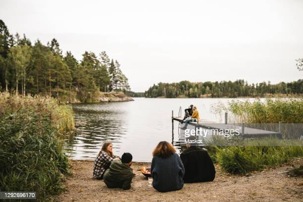 rear view of male and female talking friends while couple sitting on pier during social gathering - sweden stock pictures, royalty-free photos & images