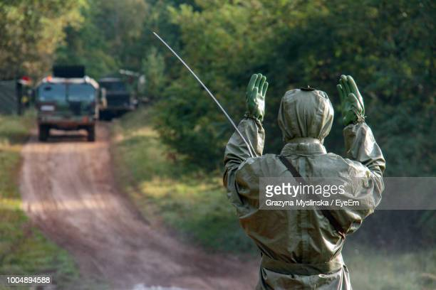 Rear View Of Male Army Soldier In Protective Workwear Gesturing Against Trucks