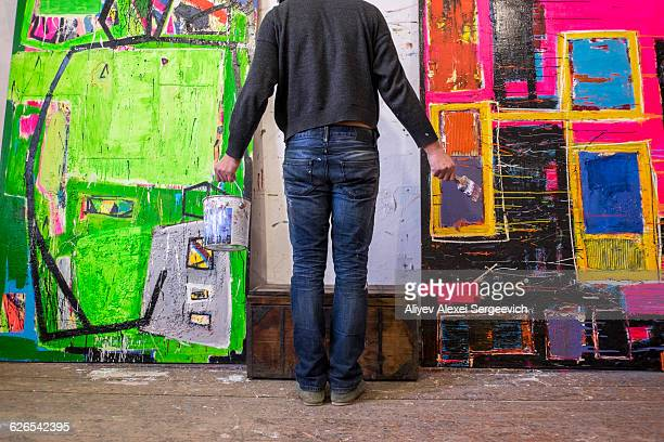 Rear view of male artist standing in front of painted canvases