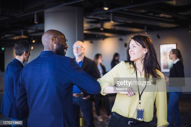 rear view of male entrepreneur greeting colleague with elbow in office - handshake stock pictures, royalty-free photos & images