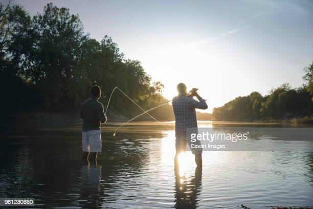 rear view of male friends fishing while standing in lake against sky - angeln stock-fotos und bilder