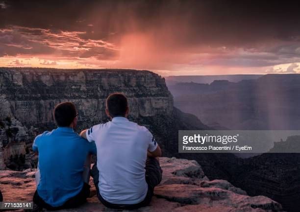 Rear View Of Male Friends Sitting On Mountain Against Cloudy Sky During Sunset