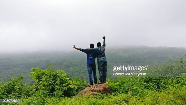 Rear View Of Male Friends Standing On Rock Against Mountains