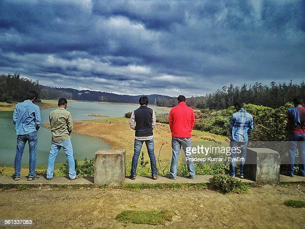 Rear View Of Male Friends Urinating In River While Standing On Bridge