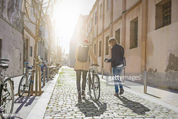 Rear view of male friends walking with bicycle