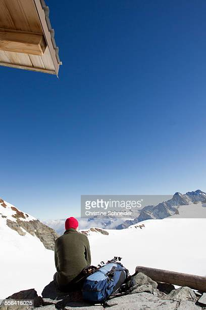 Rear view of male hiker looking out at landscape from viewing platform, Jungfrauchjoch, Grindelwald, Switzerland