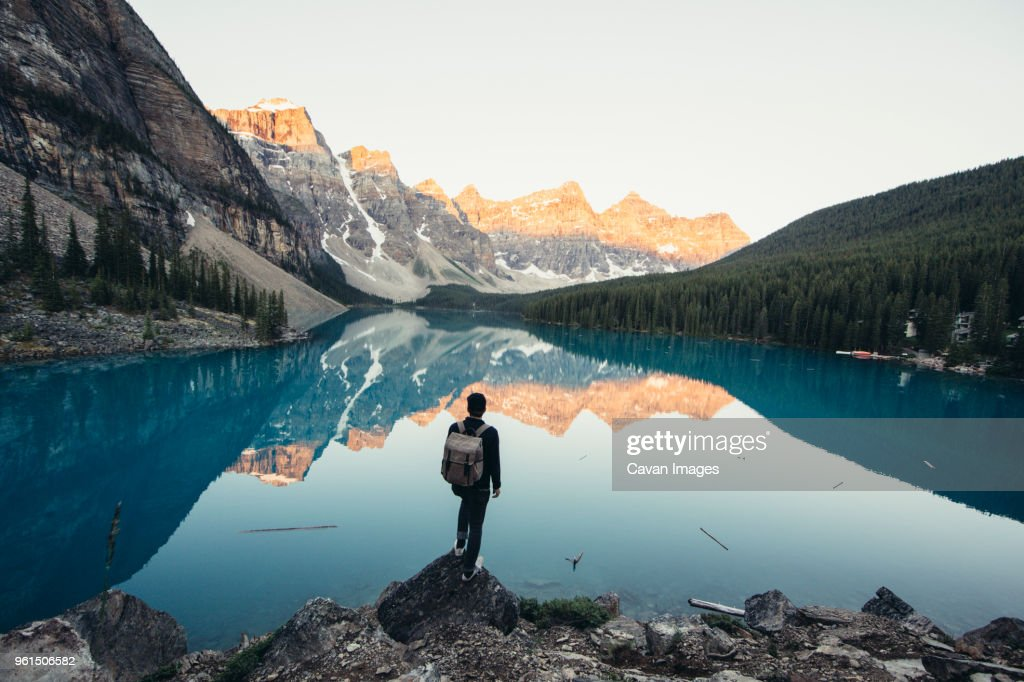 Rear view of male hiker standing by calm lake and mountains during winter : Stock Photo