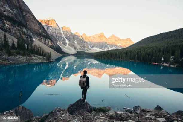 rear view of male hiker standing by calm lake and mountains during winter - reflection lake stock photos and pictures